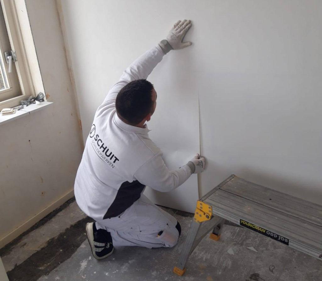 Schuit Schilderwerken verzorgt het behangen in een slaapkamer